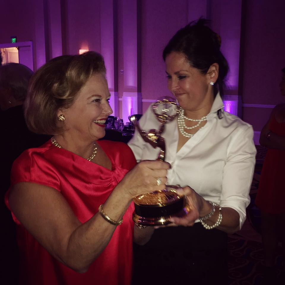 Rosemary Trible and Mari Bonnemaison holding the emmy their team won