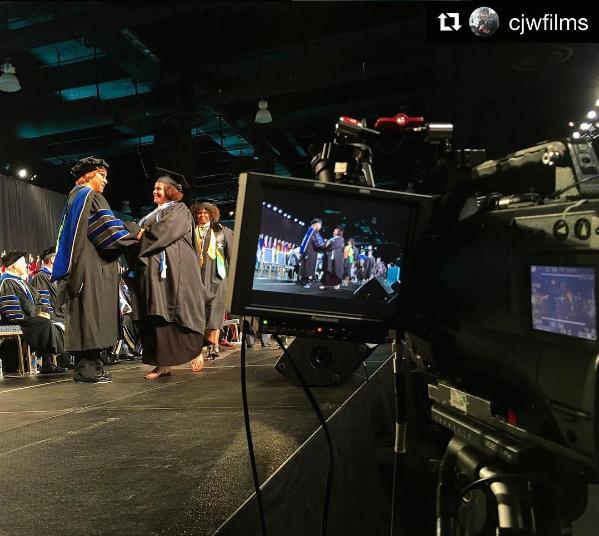 Graduates on stage being filmed for Walden University